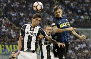 Inter Milan's Mauro Icardi, right, scores on a header past Juventus' Mario Mandzukic, left, and Leonardo Bonucci, center, during the Serie A soccer match between Inter Milan and Juventus at the San Siro stadium in Milan, Italy, Sunday, Sept. 18, 2016. (AP Photo/Antonio Calanni)